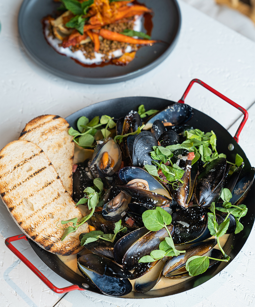 a bowl of mussels in white wine sauce