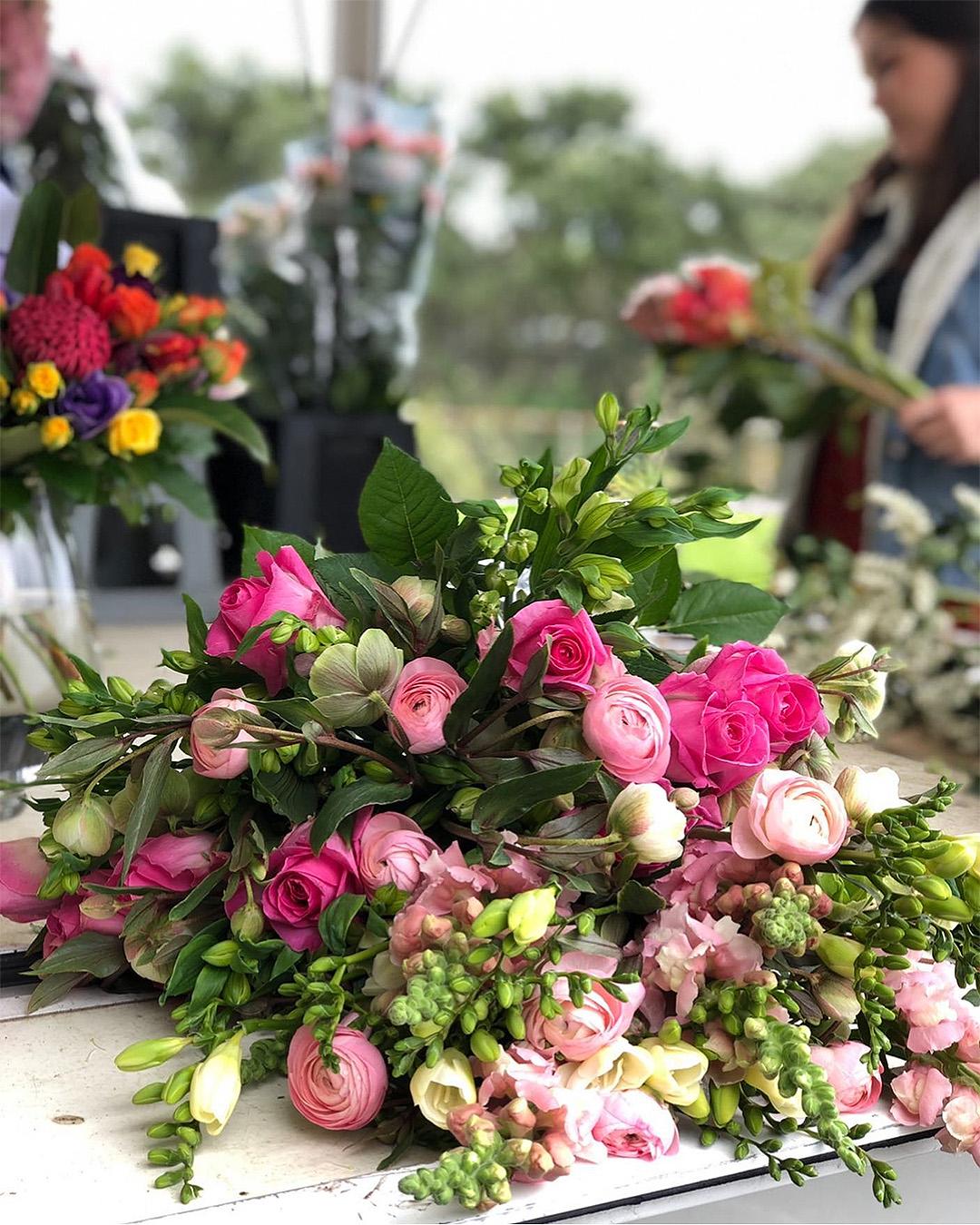 A person at La Femme Fleur flower truck makes an arrangement.