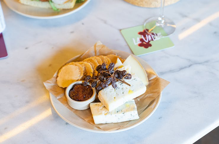 a cheese board with a glass of wine
