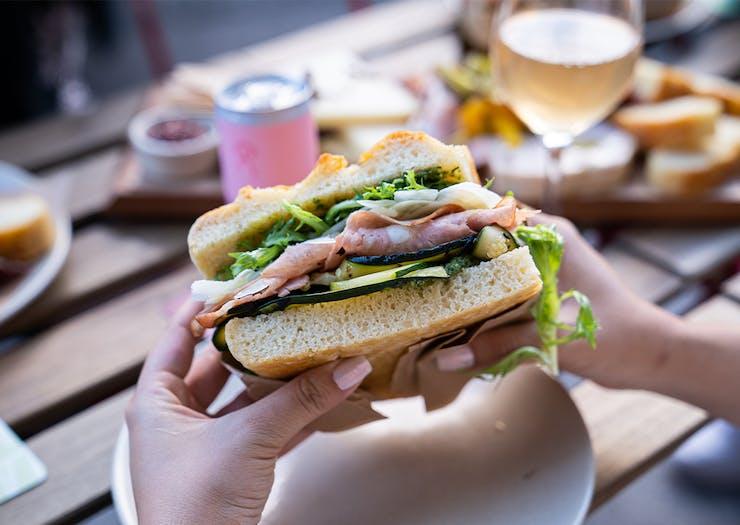 hands holding a focaccia sandwich