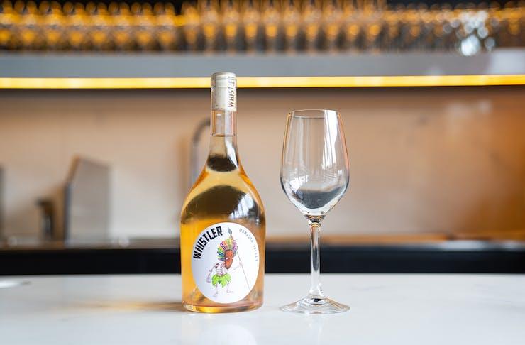 a bottle of pet nat wine on a bar