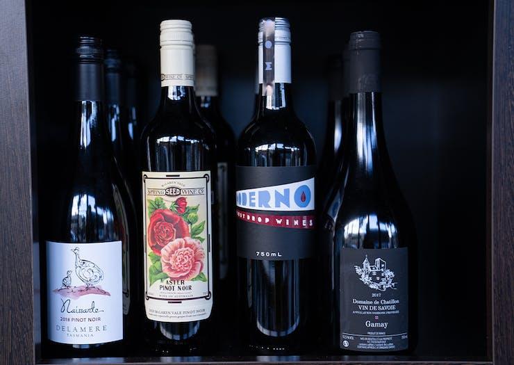 four bottles of wine on a shelf