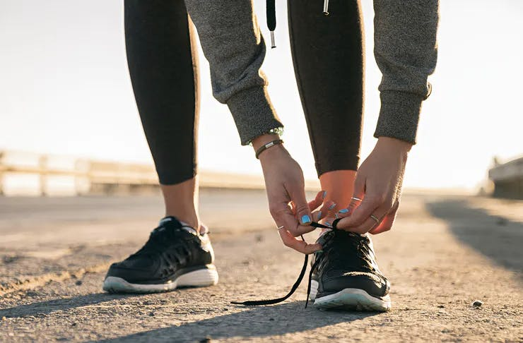 A woman bends to tie up her shoe laces before going for a run.