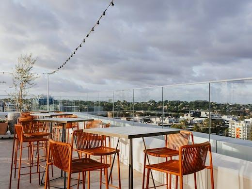 Orange bar stools on a rooftop bar
