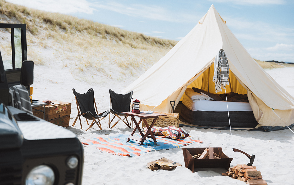 A bell tent with bed visible inside, fire pit, chairs and the side of a cool looking truck.