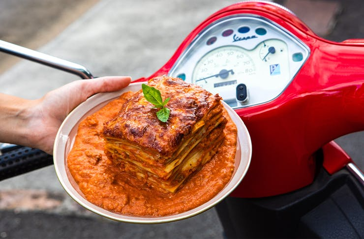 a plate of saucy lasagne in front of red scooter