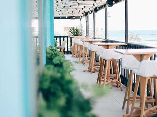 The pastel interior of Las Palmas in Palm Beach with a blurry ocean view in the background.