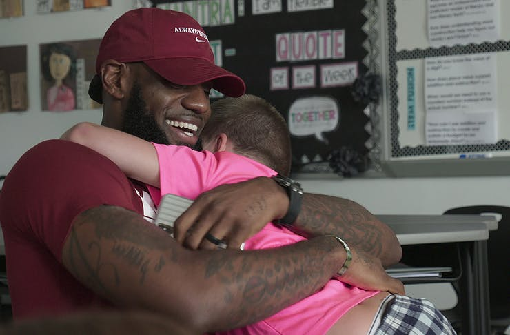 LeBron James gives a wholehearted hug to a little boy.