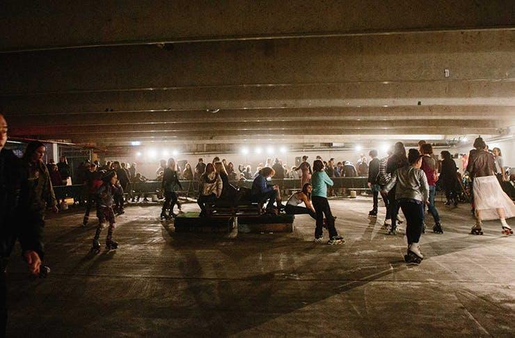 People rollerskating in an underground carpark.