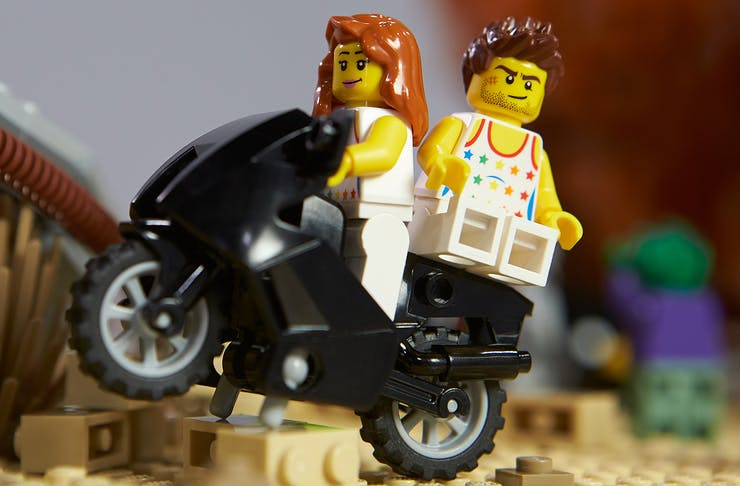 A male and female LEGO figure sit on the back of a bike.