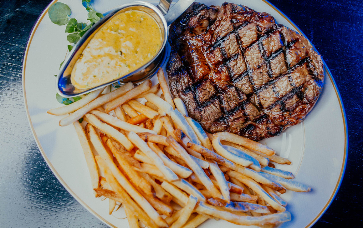 A steak with chips and sauce.