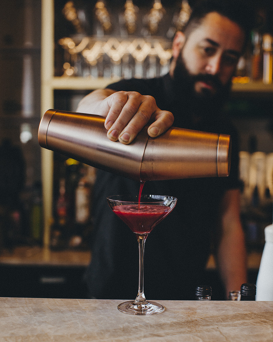 A bartender prepares a drink with panache at Little Culprit.