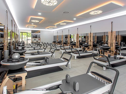 The bright interior of the Live Pilates studio with various empty Pilates machine arranged in rows.