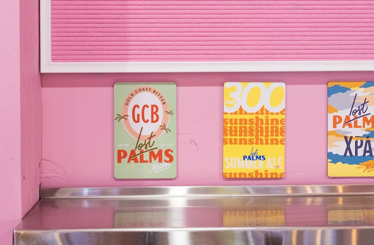 a row of tap signs on a pink wall