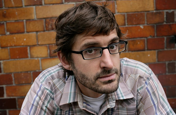 Louis Theroux looking closely at the camera in front of a brick wall.