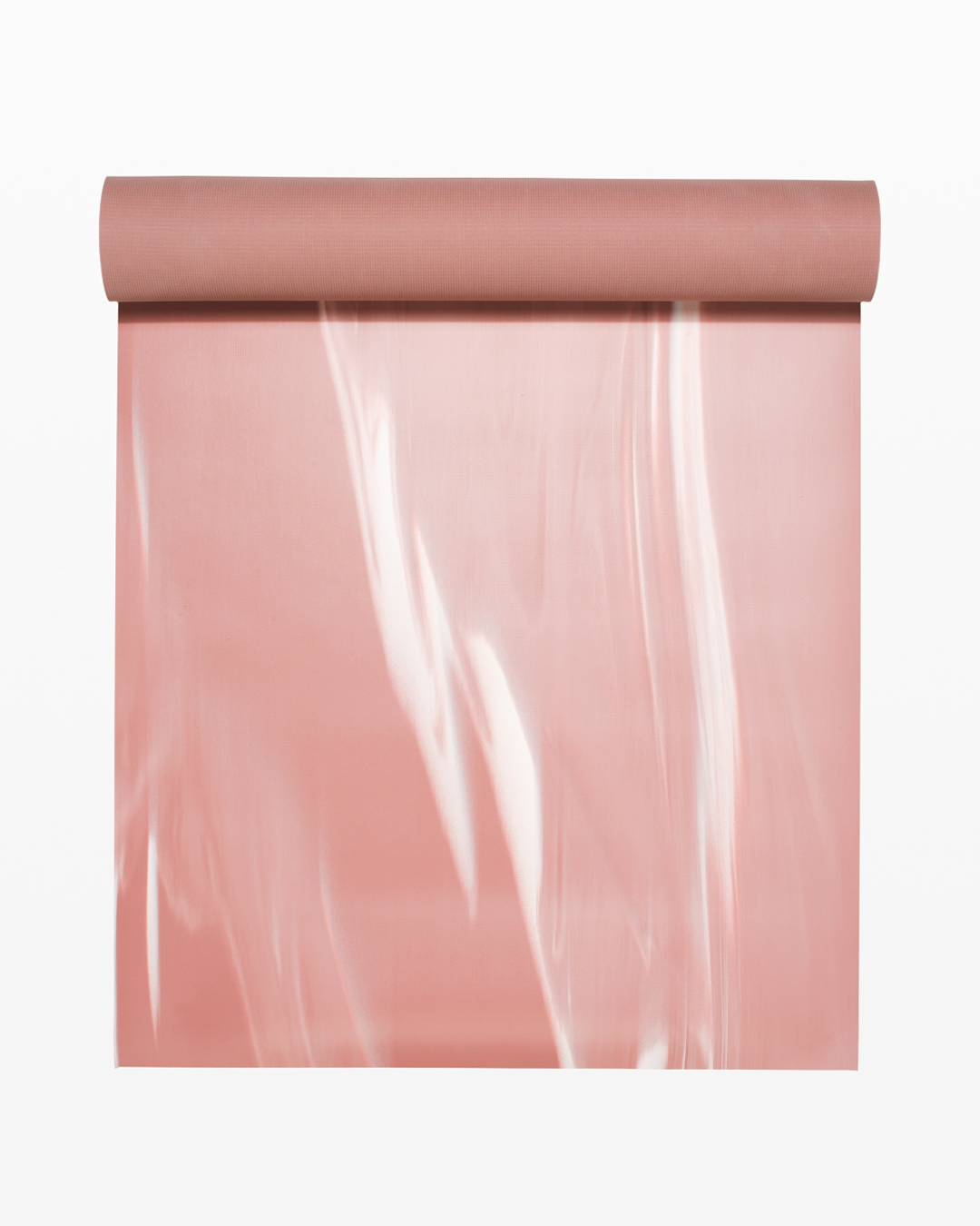 A pink yoga mat, half rolled out showing white paint stroke details