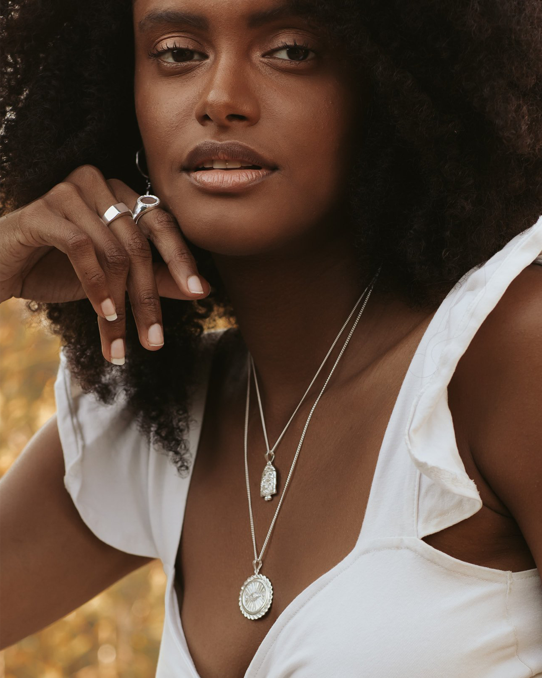 A model wearing a white top and necklaces from Luna & Rose