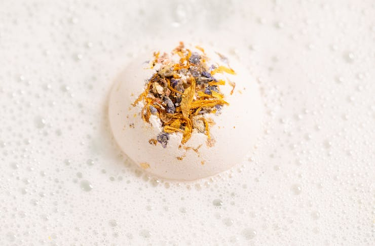 A white bathbomb in a bath filled with white bubbles
