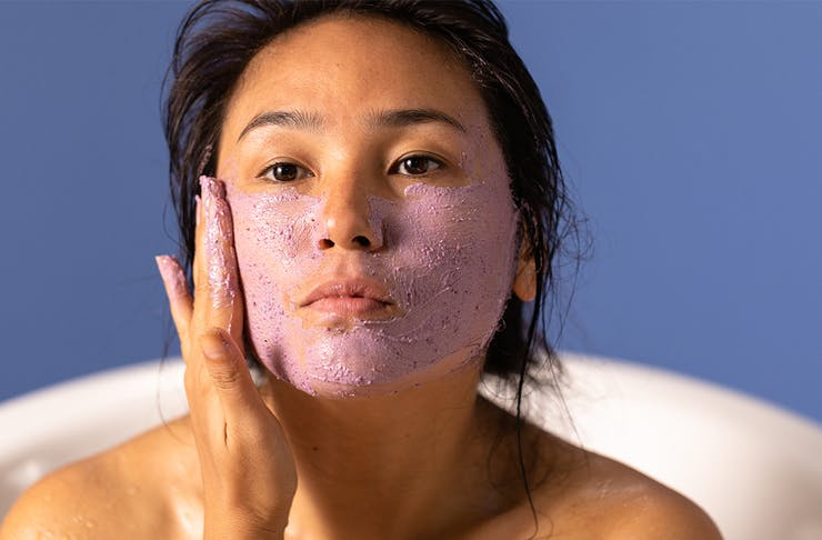 a woman rubbing a purple clay mask on her face