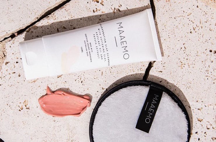 Bottle of MAAEMO pink clay cleanser lying next to a smear of the cleanser and a face cleansing pad