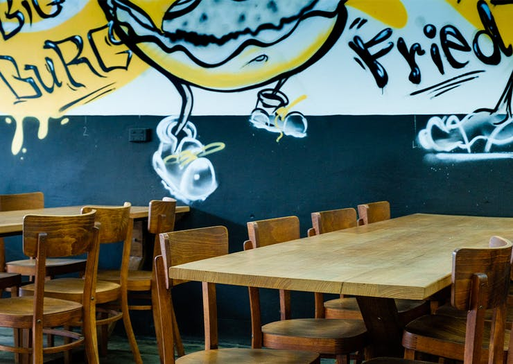 tables below a wall covered with graffiti