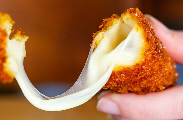 a deep fried mozarella stick being pulled apart