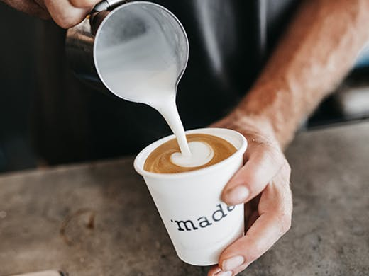 A close-up of two hands holding a white coffee cup that says 'made' on it while pouring frothing milk in the cup.