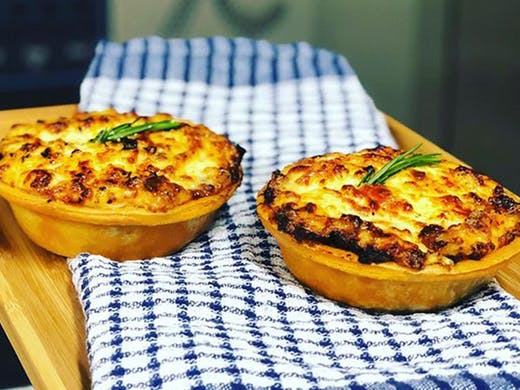 Two just-baked moussaka pies just out of the oven, placed on a wooden board.