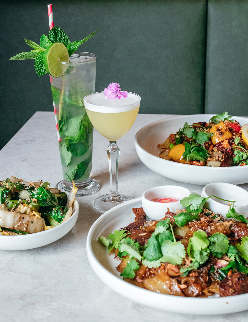 several dishes of food and two cocktails on a table