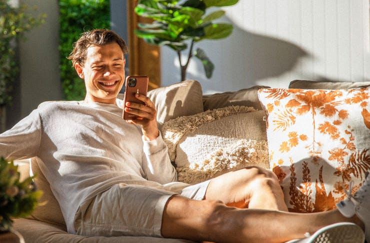 A father reclining with a Maison de Sabre phone case.