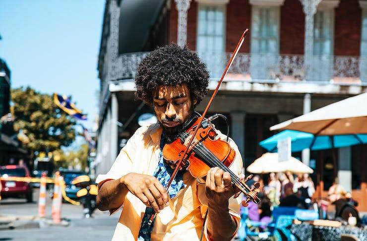 A man plays his violin in the street.