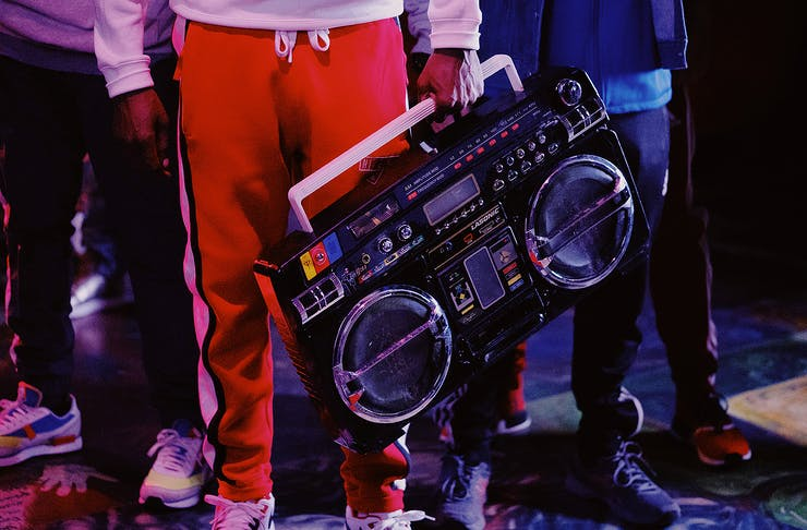 Man in red trackies holds an old school beatbox.
