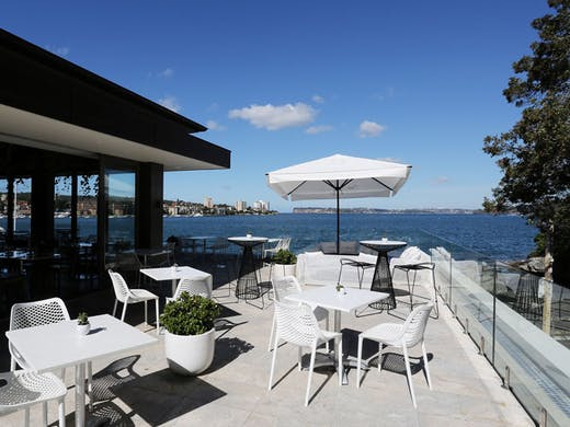 The sunny balcony at Manly Pavilion, with white chairs and a white umbrella.