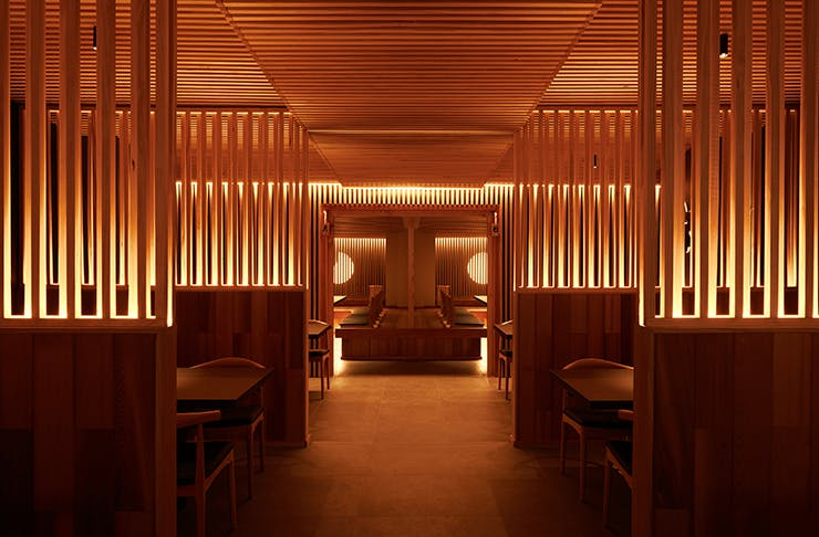 An opulent Japanese diner dimly-lit by warm lighting and wooden surroundings.