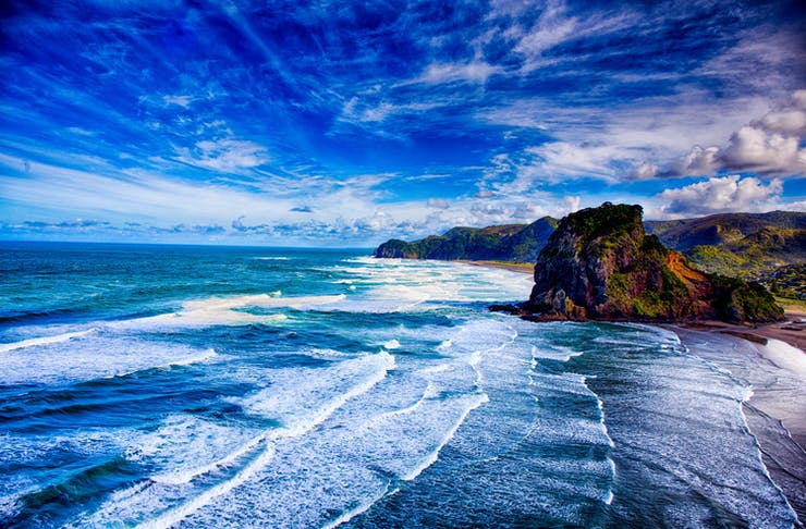 Beautiful blue sky meets an even bluer ocean, as waves crash against the beach.