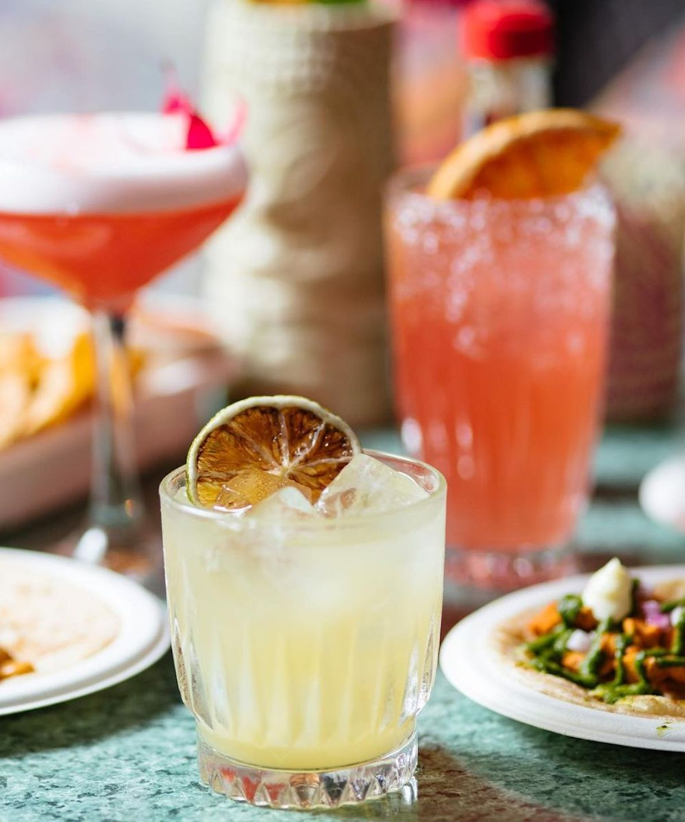 A tommy margarita surrounded by other Mexican food and drinks at Cabalitos