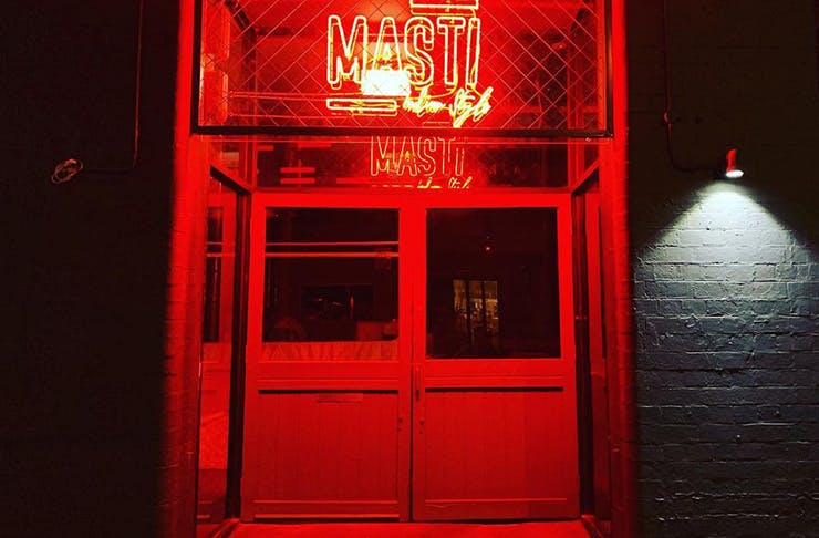 A neon-lit interior with a red neon sign that reads