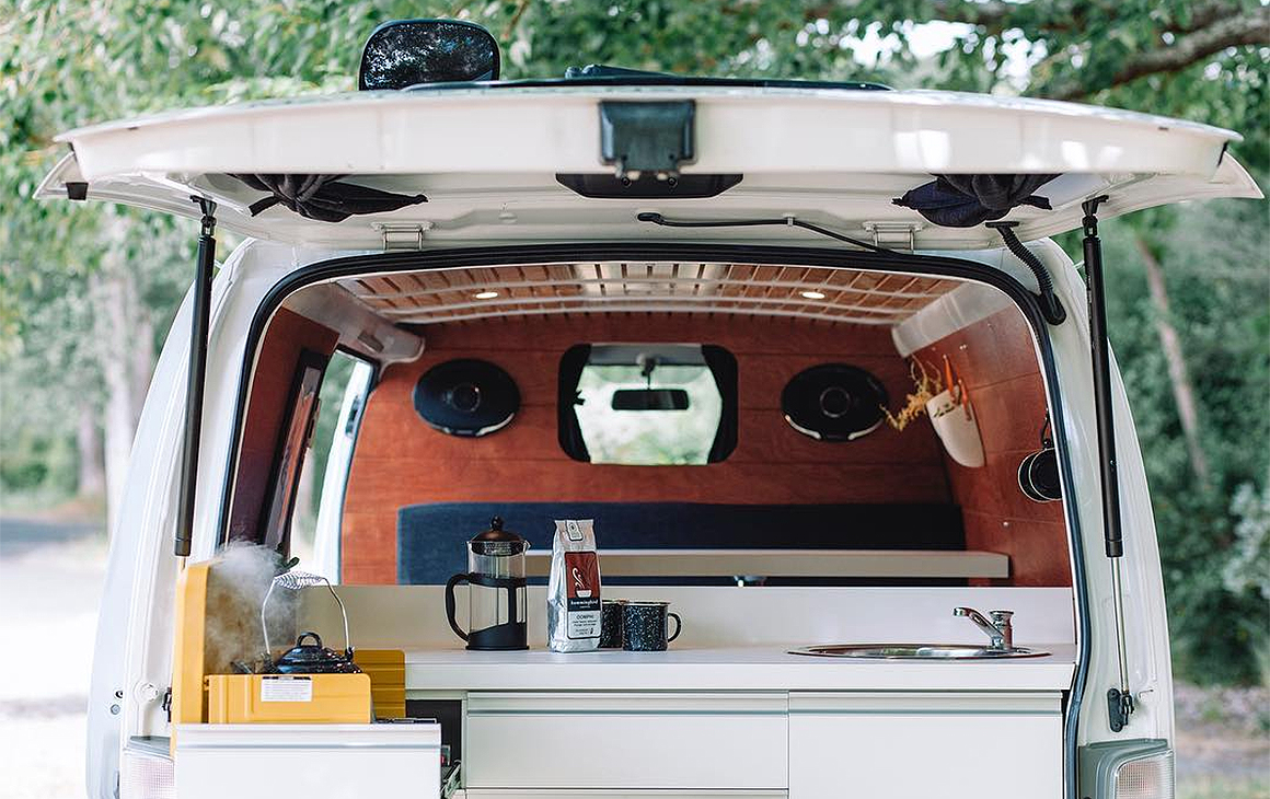 The back view of one of Matt and Dan's campervans showing a sink with a kettle on the boil.
