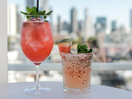 Two cocktails in front of a distant city skyline.