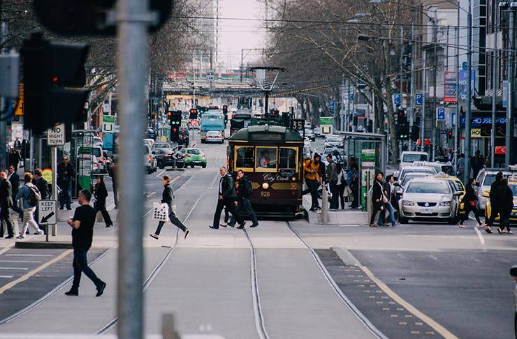 A busy Melbourne street with a tram shuttling through the middle.
