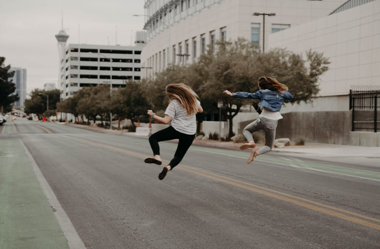 Two girls happily jumping in the middle of the road.