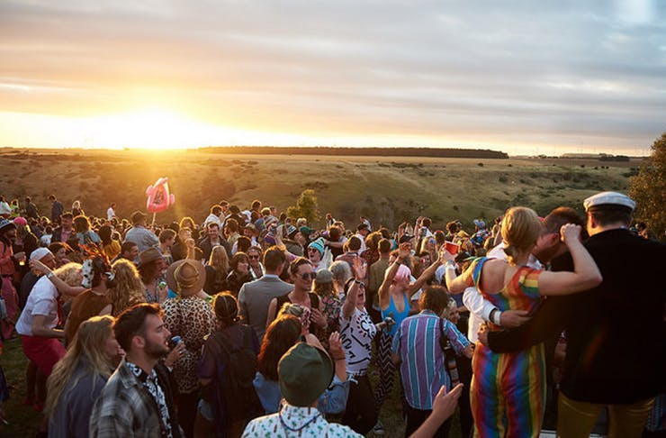 Festival-goers at Meredith overlooking the sunset across several grassy paddocks.