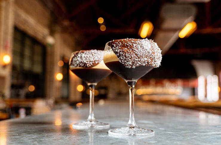 Two espresso martinis on a marble table. Chocolate is dripping from the rim of the glass.