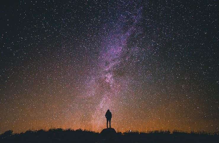 Person in silhouette standing against a star-filled sky