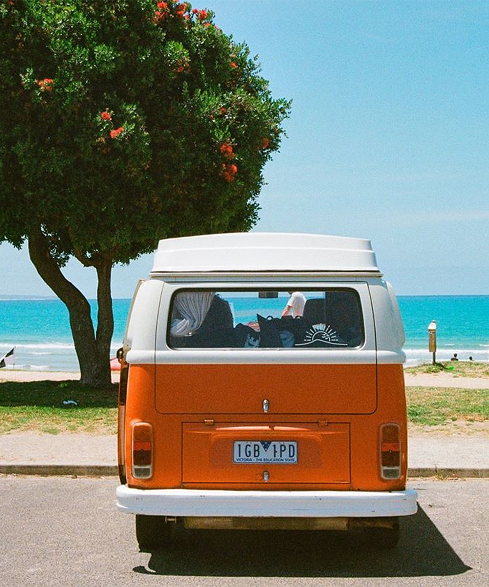 A cute little Mighway orange combi sits on the seaside.