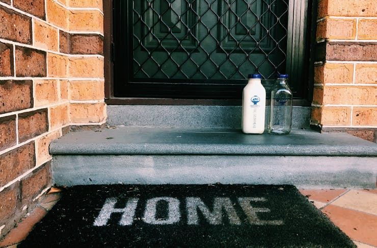 A glass bottle filled of milk sitting on a doorstep. A doormat sits in front with the words
