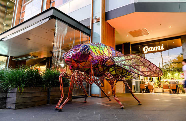 A large colourful insect part of an art installation.