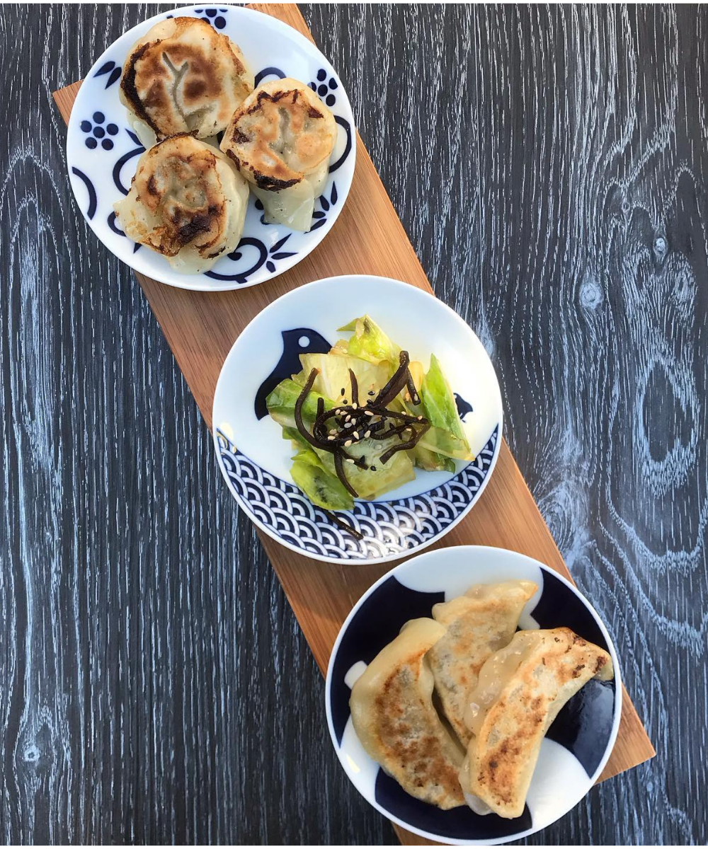 Two plates of gyoza (Japanese dumpling) and a plate of pickles to refresh the palette.
