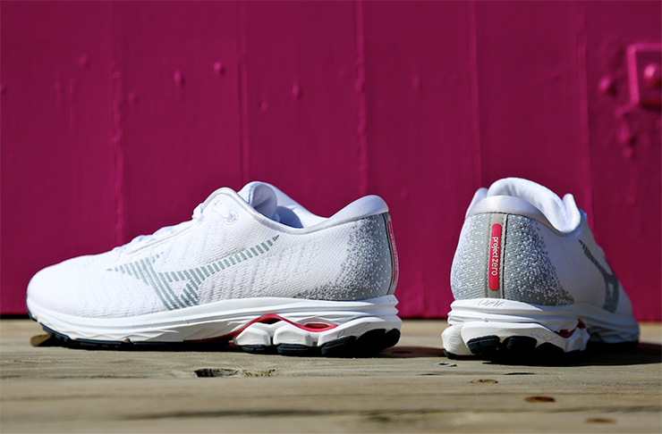 A white pair of running sneakers with pink accents in front of a pink wall.