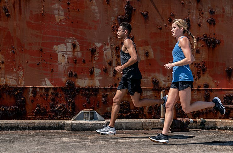 Two people running along industrial docks.